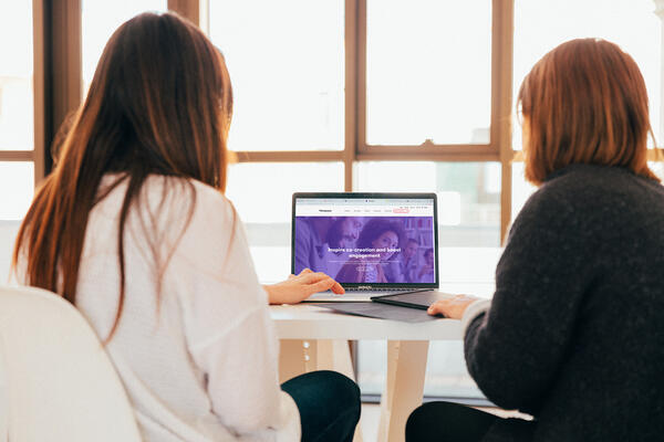 Two women looking at a laptop together